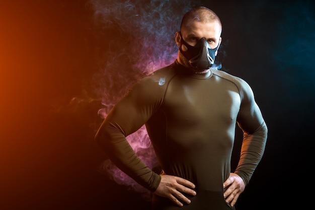 Un forte sportivo dai capelli scuri con una maglietta sportiva verde e una maschera da allenamento in posa su uno sfondo di fumo blu e rosso vape su un nero isolato