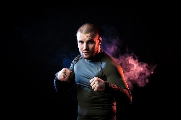 Un forte sportivo dai capelli scuri in un abbigliamento sportivo verde in posa su uno sfondo di fumo blu e rosso vape su un nero isolato