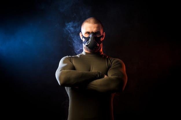 Un forte lottatore sportivo dai capelli scuri in una maglietta sportiva verde e una maschera da allenamento si erge con le braccia incrociate con sicurezza su uno sfondo di fumo blu e rosso vape su un nero isolato