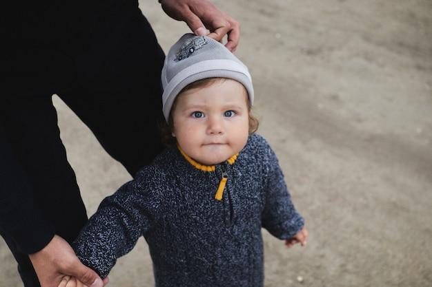 Mano forte del padre che tiene una piccola mano di suo figlio. padre e figlio stanno camminando nel parco