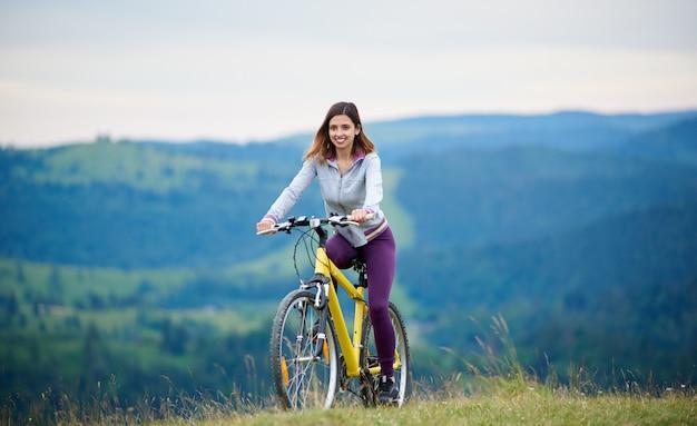 Motociclista femminile forte in bicicletta su mountain bike giallo su un sentiero rurale la sera. montagne sullo sfondo sfocato. attività sportiva all'aperto, concetto di lifestyle