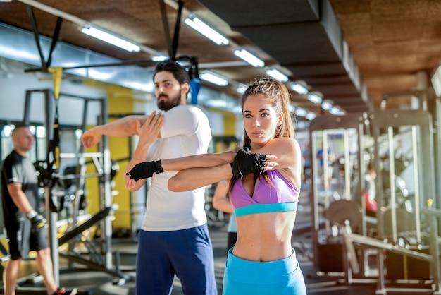Coppia giovane in forma forte che allunga i muscoli dopo l'allenamento in palestra.