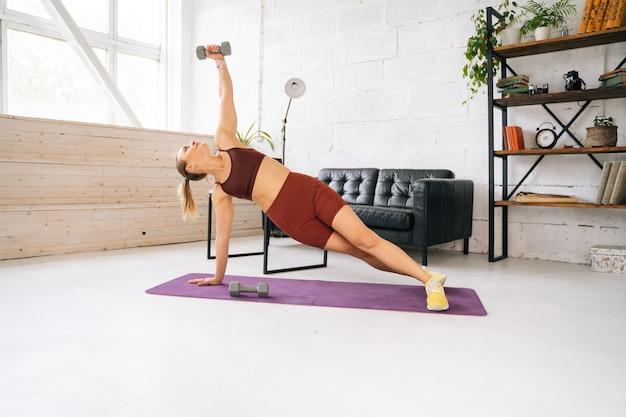 Giovane donna in forma forte con un corpo atletico perfetto che indossa abbigliamento sportivo facendo tavola laterale con manubri durante l'allenamento. concetto di stile di vita sano e attività fisica a casa.