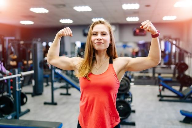 Forte donna di forma fisica che mostra la forza dei muscoli bicipiti. fit modello di fitness ragazza isolato su sfondo nero.