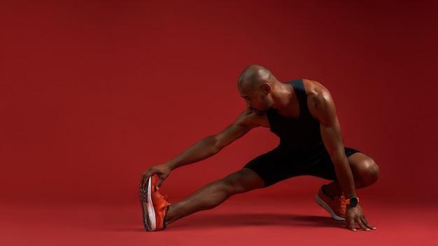 Giovane africano forte e flessibile in abbigliamento sportivo che allunga le gambe mentre sta in piedi contro il rosso