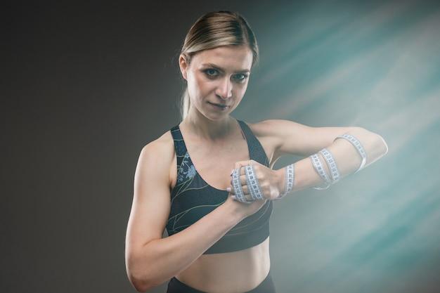 Ragazza forte in abiti sportivi con un nastro di centimetro sulla mano su un muro nero con riflesso lente