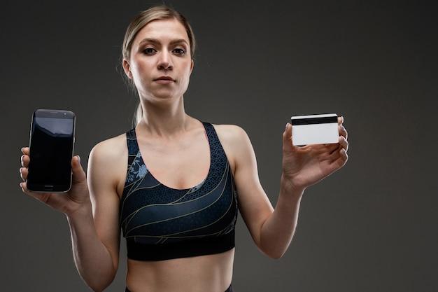 Ragazza forte in abiti sportivi con una carta di credito e un telefono su un muro scuro