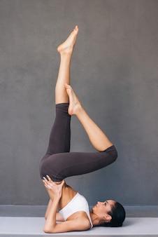 Forte e grazioso. vista laterale della bella giovane donna africana in abiti sportivi che praticano yoga sul tappetino da ginnastica su sfondo grigio gray