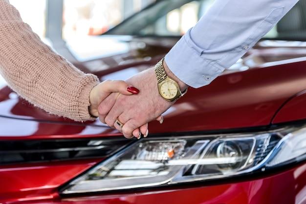 Forti strette di mano sullo sfondo dell'auto. affare per l'acquisto di auto