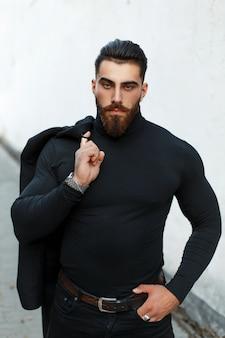 Forte uomo bello in un cappotto nero in una camicia nera con barba e baffi in posa per strada