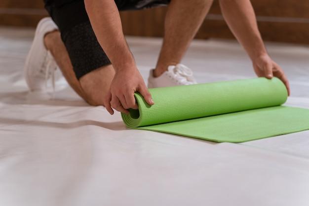 Forte bel giovane, un atleta, si srotola un tappetino, preparando un posto per lo sport. ragazzo determinato che fa allenamento fisico.