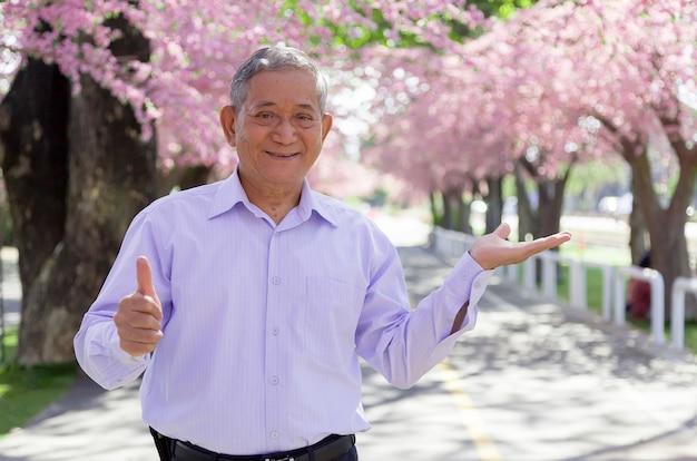 L'uomo anziano asiatico forte e felice tumb up e apre il prodotto presente della mano sul parco del fiore