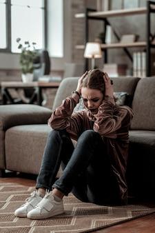 Forte mal di testa. adolescente che ha un forte mal di testa dopo una grande depressione mentre è seduto sul pavimento