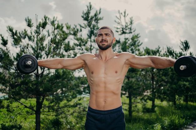 Un uomo forte e sano allunga le braccia, fa sollevamento pesi ed esercita i bicipiti con i bilancieri