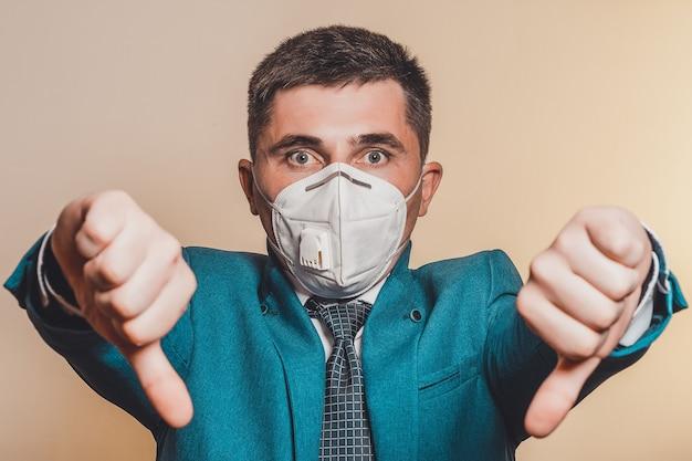 Uomo forte, uomo d'affari in cravatta e mascherina medica dimostra fiducia al lavoro contro una pandemia di coronavirus.