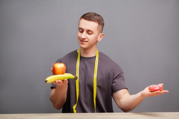 L'uomo forte consuma un pasto ad alto contenuto proteico di carne e ciambella.