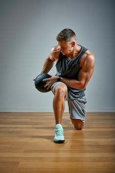 Uomo forte che fa esercizio con la palla medica. fisico perfetto per uomo su grigio. forza e motivazione.