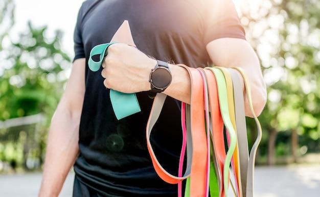 Uomo forte ragazzo che tiene insieme di elastici colorati elastici allo stadio all'aperto. atleta di sesso maschile durante l'allenamento con attrezzatura sportiva aggiuntiva