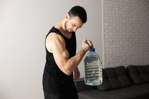 Un uomo forte sta facendo esercizi di sollevamento dei polpacci con una grande bottiglia d'acqua a casa nel suo appartamento spazioso e luminoso con interni minimalisti. uomo in abiti sportivi neri che fanno allenamento mattutino.