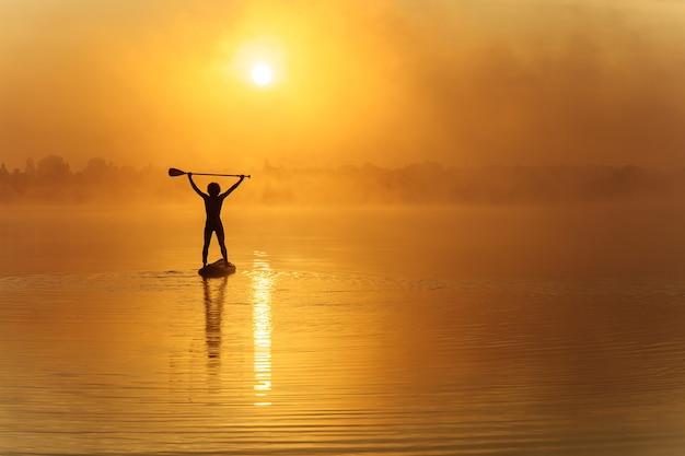 Uomo forte in costume da bagno in piedi sulla tavola sup con pagaia sopra la sua testa durante la luce del mattino sul lago