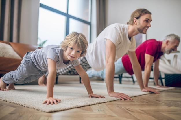 Uomo forte. due uomini e il loro figlio in piedi sulla plancia