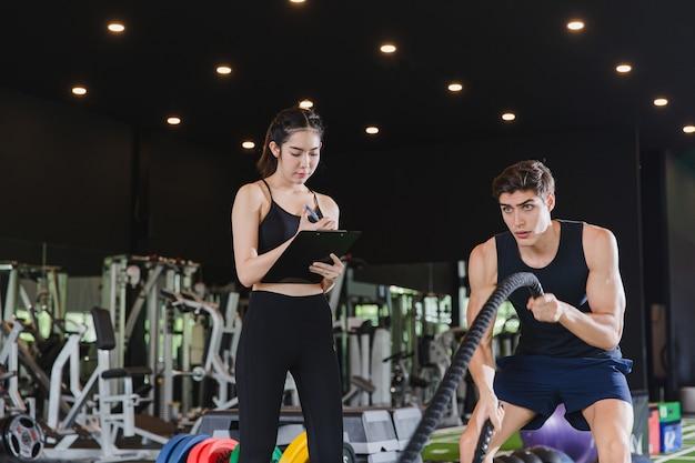 Uomini forti con corde da battaglia con corde da battaglia si esercitano in una palestra di fitness funzionale con un istruttore femminile. allenamento in palestra e concetto di fitness