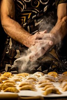 Forti mani da uomo cospargono gnocchi di farina piatto nazionale ucraino