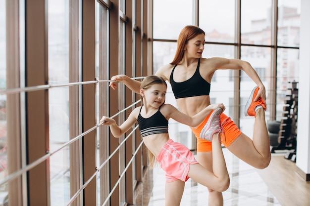 La madre forte e sua figlia sono impegnate in fitness, esercizio fisico e stretching in palestra