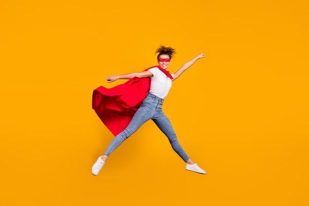Forte ragazza in forma motivata che salta indossando il mantello