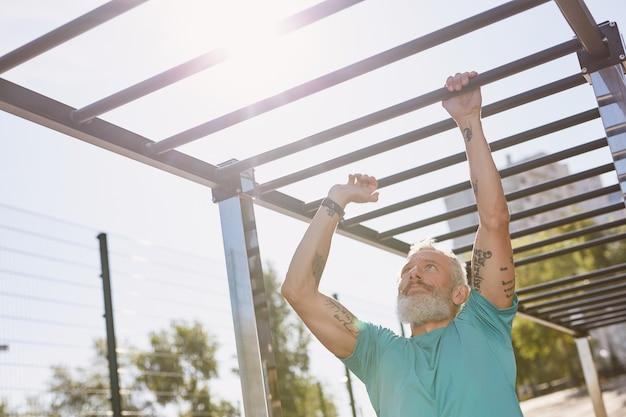 Muscoli forti uomo anziano con tatuaggi sulle braccia che si arrampicano sulle barre delle scimmie mentre si allenano