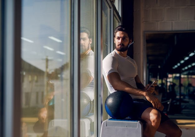 Forte uomo muscoloso seduto vicino alla finestra con il cellulare in mano e una grande palla accanto a lui e guardando lontano.