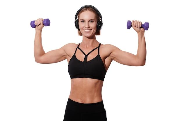 Forte sportiva muscolare in cuffie e vestito nero che fa esercizio con i dumbbells sopra fondo isolato bianco