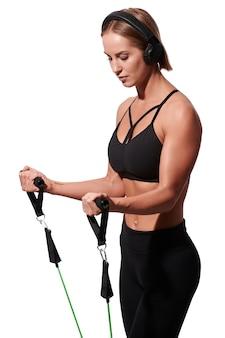 Forte sportiva muscolare in cuffie che si esercita con la fascia di resistenza sopra fondo isolato bianco