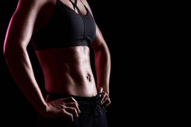 Addominali forti della donna perfetta dopo l'allenamento. corpo femminile snello e muscoloso con gocce di sudore