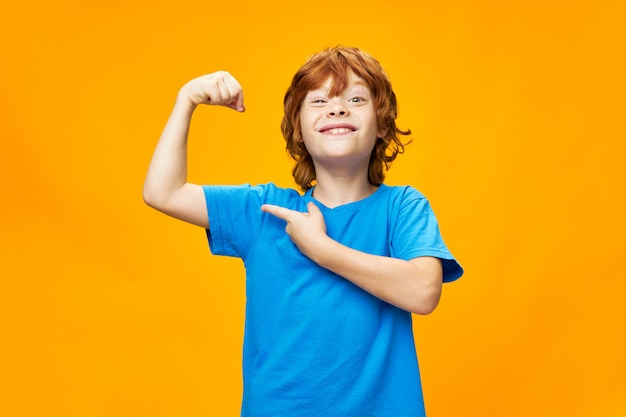 Forte ragazzo dai capelli rossi con una maglietta blu su un giallo mostra i muscoli delle sue braccia