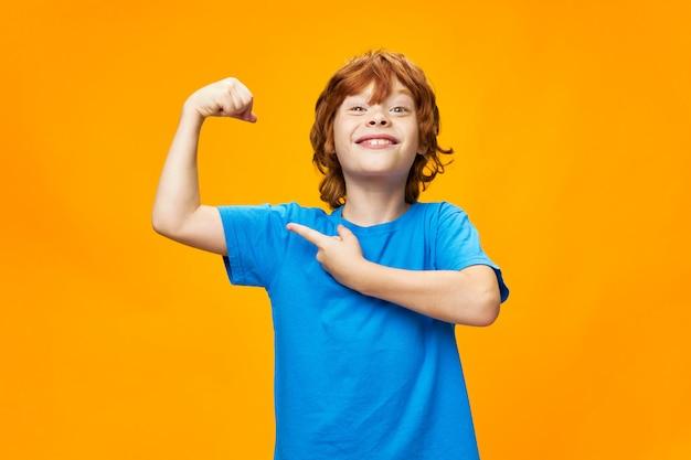 Forte ragazzo dai capelli rossi indica i muscoli delle sue braccia