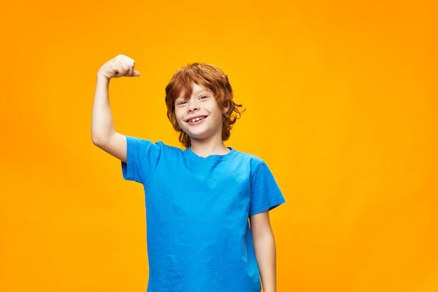 Forte bambino dai capelli rossi mostra i muscoli delle braccia e la maglietta blu gialla