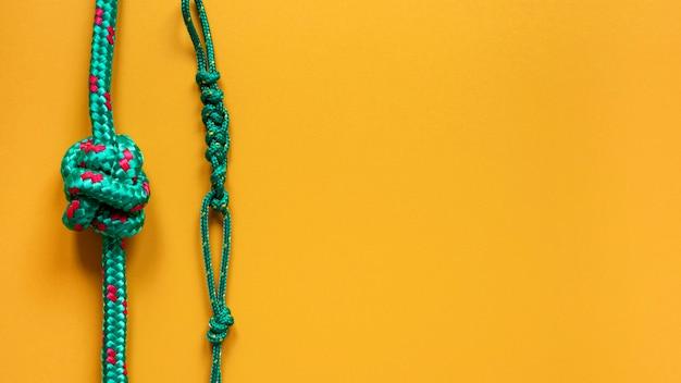 I nodi forti della corda copiano il fondo giallo dello spazio