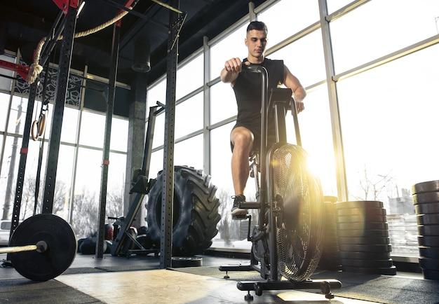 Forte, autocontrollo. giovane atleta caucasico muscolare che si allena in palestra, fa esercizi di forza, pratica, lavora sulla parte inferiore del corpo con la ruota che rotola. fitness, benessere, concetto di stile di vita sano.