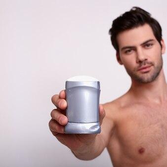 Il forte uomo sexy tiene il deodorante a bianco
