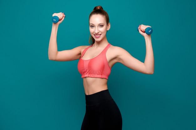 Forte allenatore di fitness sorridente con manubri su sfondo verde isolato