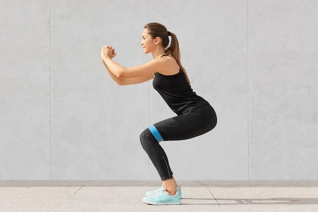 La forte donna caucasica sportiva ha esercizi con elastico in gomma, allena le gambe, lavora sui muscoli, vestita in maglietta e leggings, sta in piedi su grigio in palestra