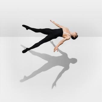 Forte giovane atleta maschio alla moda sul fondo bianco dello studio con le ombre nel salto