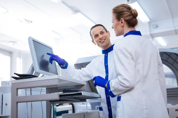 Squadra forte. un paio di ricercatori discutono di un caso medico interessante mentre lui indica lo schermo e le sorride