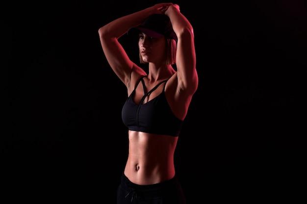 Forte donna che indossa reggiseno sportivo con addome muscoloso su sfondo nero forma perfetta del corpo