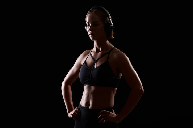Forte donna che indossa reggiseno sportivo con addome muscoloso ascolta musica in cuffia su sfondo nero forma perfetta del corpo