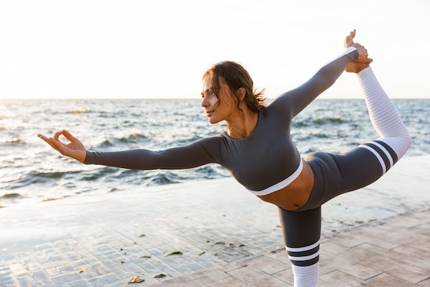 Allungamento forte della giovane donna di forma fisica