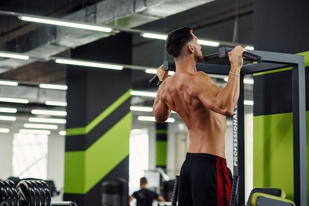 Il giovane forte fa il pull-up sulla traversa durante l'allenamento nella moderna palestra. vista posteriore.