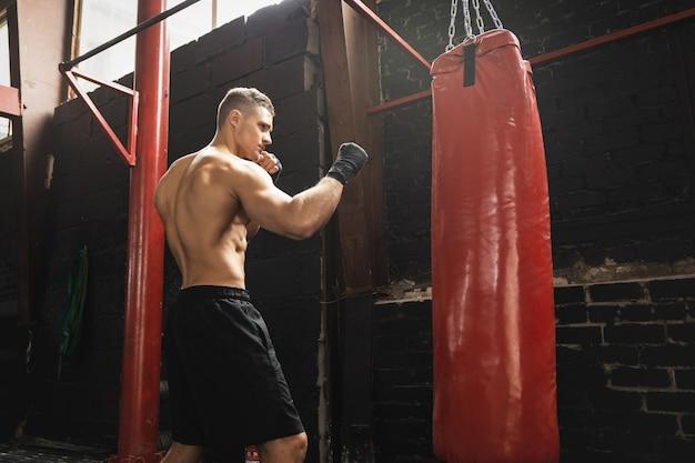 Combattente giovane e forte di mma e sacco da boxe rosso