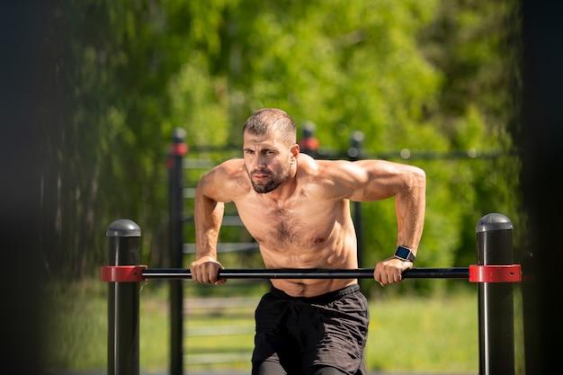 Forte giovane sportivo in topless che tiene dal bar dello sport mentre si china su di esso durante l'allenamento all'aperto